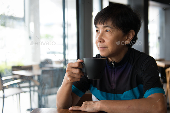 Senior Asian woman with coffee in cycling jersey - Stock Photo - Images