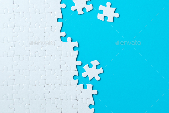 Jigsaw puzzle pieces on blue background - Stock Photo - Images