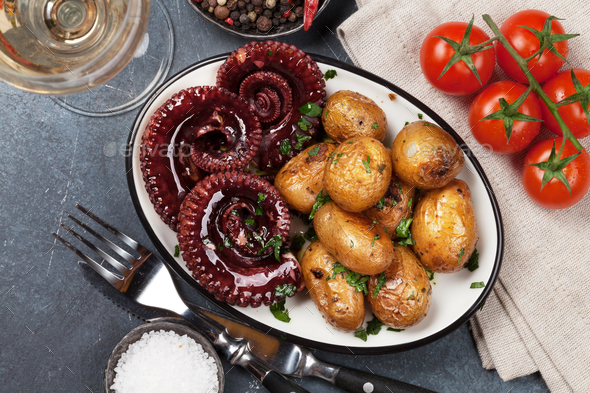 Grilled octopus with small potatoes and wine - Stock Photo - Images