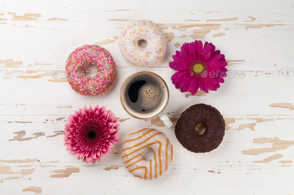Coffee cup, donuts and gerbera flowers - Stock Photo - Images