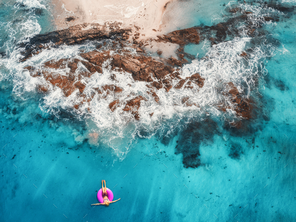 Aerial view of young woman swimming on the pink swim ring in the transparent turquoise sea - Stock Photo - Images
