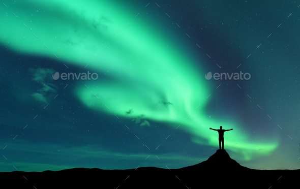Aurora and silhouette of standing man with raised up arms on the mountain in Norway - Stock Photo - Images