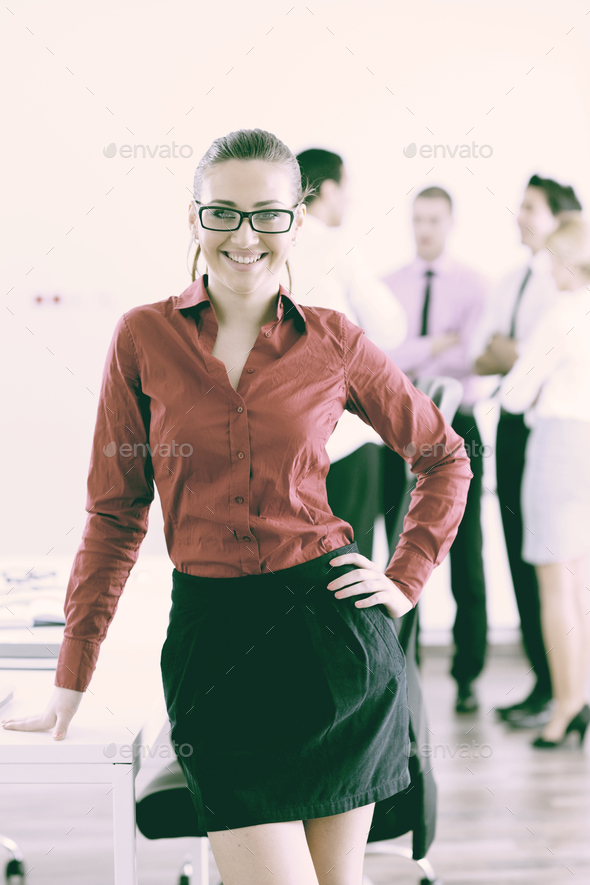 business woman standing with her staff in background - Stock Photo - Images