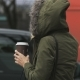Hooded Young Woman in Green Jacket Holding a Coffee Bin - VideoHive Item for Sale