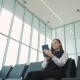 Side Portrait of Smiling Asian Businesswoman Sitting with Laptop, Mobile Phone and Luggage at