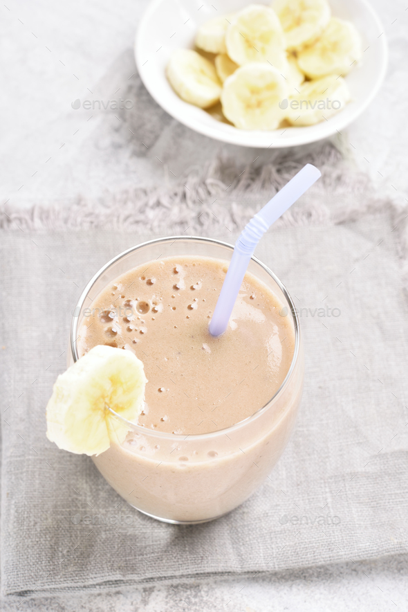 Healthy drink milkshake with banana in glass on stone table. - Stock Photo - Images