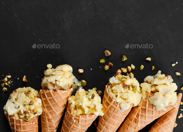 Vanilla ice cream in waffle cone with nuts on black - Stock Photo - Images