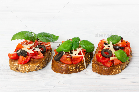 Bruschetta with fresh tomato, basil, cheese and olive - Stock Photo - Images