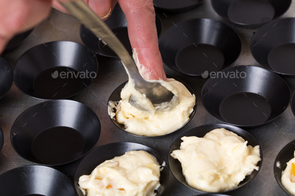 Taking muffin dough to baking pan. - Stock Photo - Images