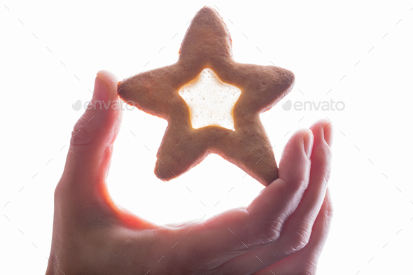 Hand holding star cookie with syrup. - Stock Photo - Images