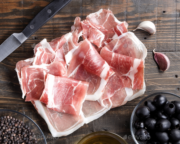 slices of Iberian ham on wooden board - Stock Photo - Images