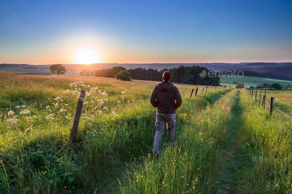 Man walking along Track Towards Sunset - Stock Photo - Images