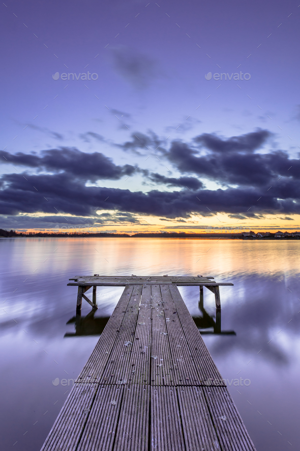 Purple Colored Sunset over Tranquil Lake with Wooden Jetty - Stock Photo - Images
