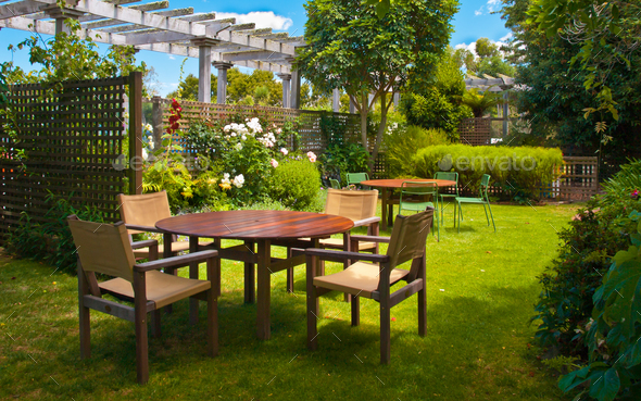 Dining Table set in Lush Landscaped Garden - Stock Photo - Images