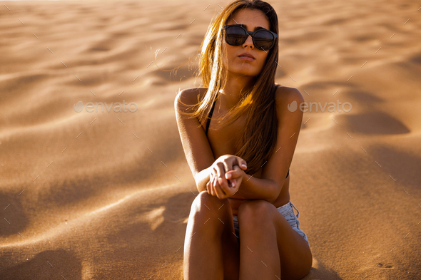 Young girl sitting on a sand dune - Stock Photo - Images