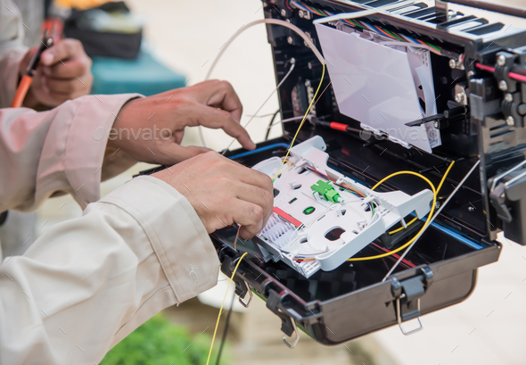 Technicians are installing fiber optic cabinets. - Stock Photo - Images