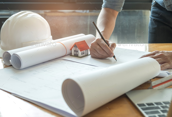 Architects are writing with Home model , Safety helmet and lapto - Stock Photo - Images