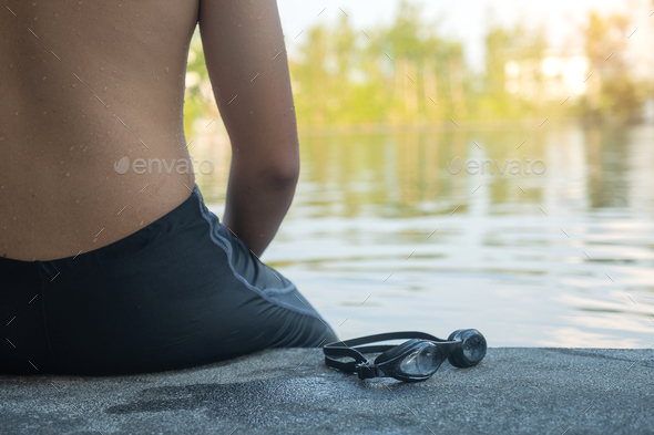 Young man wearing swimsuit sitting by the pool,Photo from the ba - Stock Photo - Images
