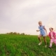 Two Carefree Girls Run Across the Green Meadow, Holding Hands. They Rejoice in the Arrival of Spring - VideoHive Item for Sale