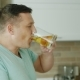 A Young Caucasian Man with Pleasure Drinks Beer in His Kitchen. Then He Smiles and Looks Into the - VideoHive Item for Sale