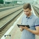A Good-looking Young Man Uses a Tablet Railroad Station - VideoHive Item for Sale