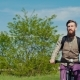 A Young Bearded Man Is Riding a Bicycle. Enjoys a Trip on a Clear Spring Day. Steadicam Shot - VideoHive Item for Sale
