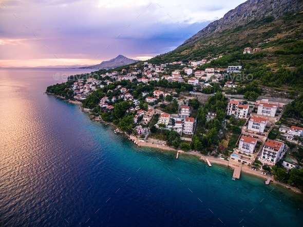 Aerial top view of a village located on a mountain by the sea at sunset in Croatia - Stock Photo - Images