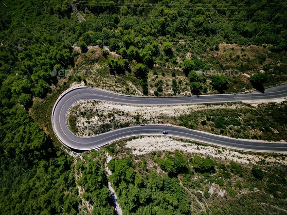Aerial view of curve road with a car on the mountain with green forest in Croatia - Stock Photo - Images