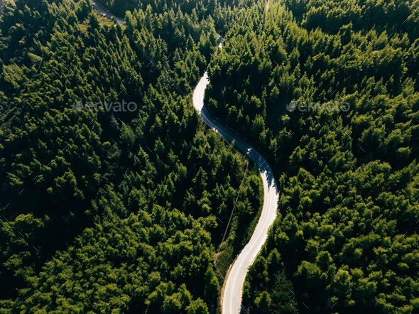 Aerial view of curve road on the mountain with green forest in Greece - Stock Photo - Images