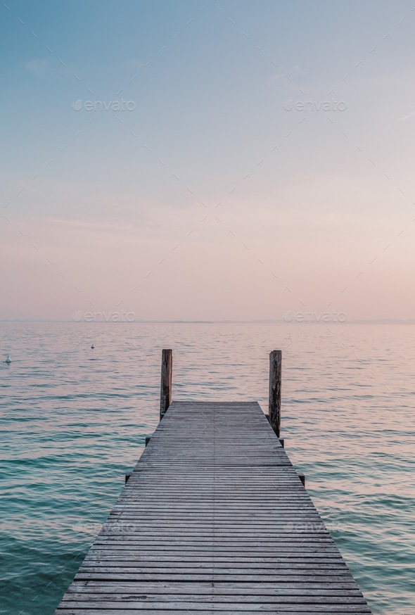 View of a wooden pier on the seashore with clear morning sky and sea with turquoise water. - Stock Photo - Images