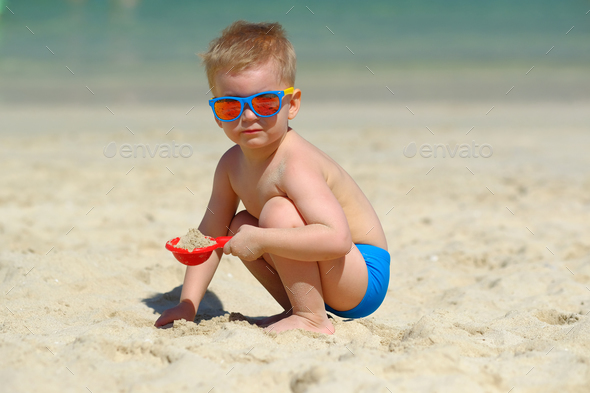 Toddler boy playing with shovel and sand on beach - Stock Photo - Images