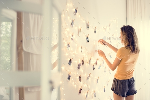 A young woman looking at photos hanging on decoration lights - Stock Photo - Images