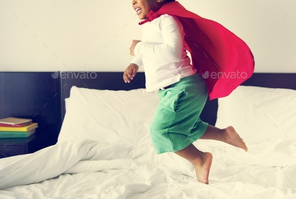 African descent kid jumping on the bed - Stock Photo - Images