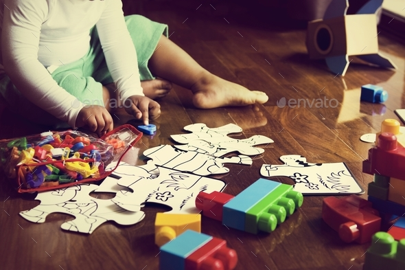 African descent kid enjoying puzzles on wooden floor - Stock Photo - Images