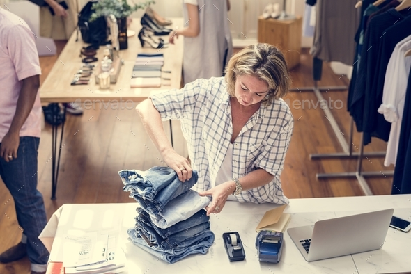 Woman folding jeans - Stock Photo - Images