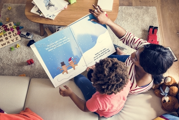 Mom reading picture book with her son - Stock Photo - Images