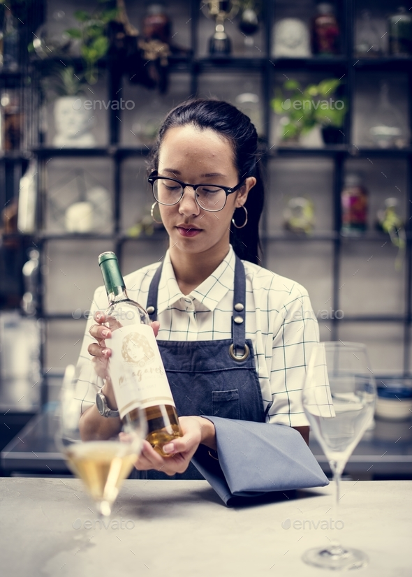 A bartender holding a wine bottle - Stock Photo - Images
