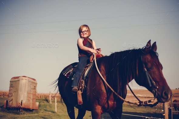 Young girl is enjoying a horse riding - Stock Photo - Images