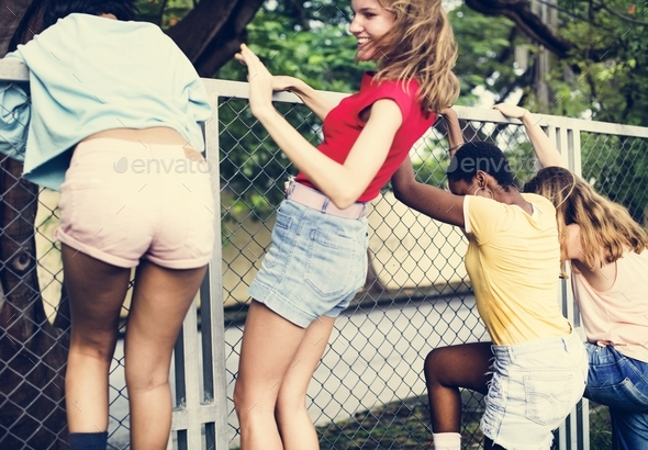 Group of women climbing over the fence - Stock Photo - Images