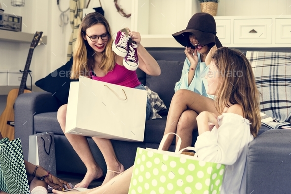 Women showing friends shopping shoes - Stock Photo - Images
