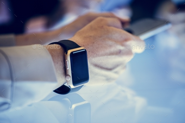 Hand with smartwatch holding smartphone - Stock Photo - Images
