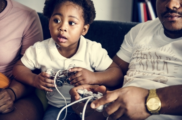 Black family playing game console together - Stock Photo - Images