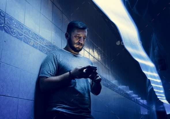 Closeup of a man using mobile phone in the dark with long exposure light - Stock Photo - Images