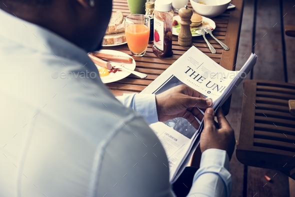 Rear view of black man reading newspaper while having breakfast - Stock Photo - Images
