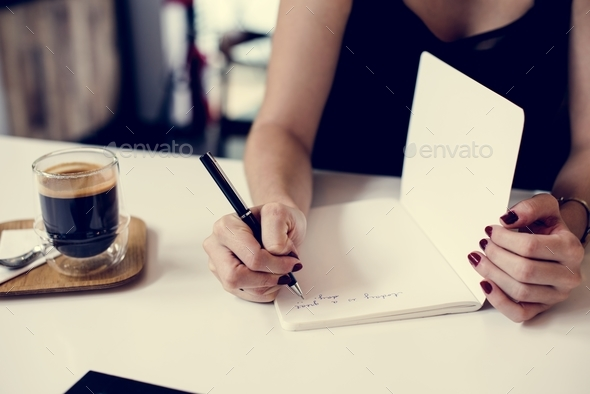 Hands writing down a note on a notebook - Stock Photo - Images