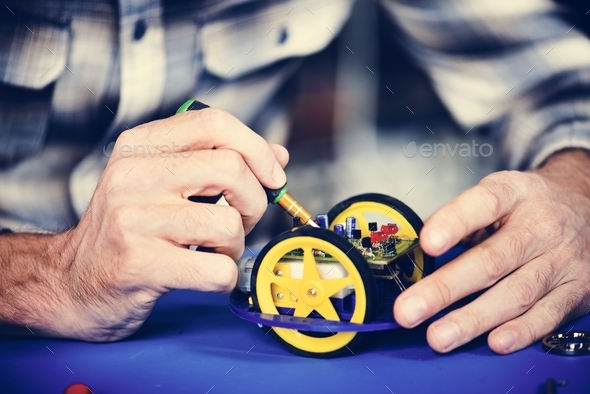 Closeup of hands working on robot wheels - Stock Photo - Images