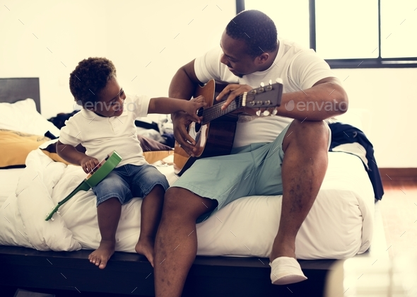 Black father enjoy playing guitar with his child together happiness - Stock Photo - Images
