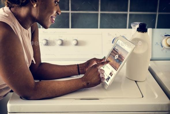 Black woman using digital tablet near the washing machine - Stock Photo - Images
