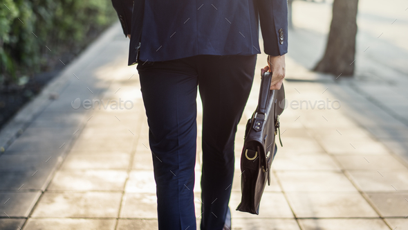 Walking business man holding his bag - Stock Photo - Images