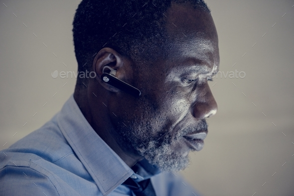 African ethnicity businessman with bluetooth earphone - Stock Photo - Images